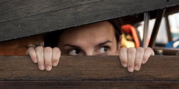 Gesicht einer Frau, die hinter einer Bretterwand steht und vorsichtig durch einen Spalt schaut