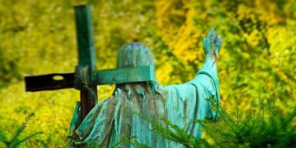 Eine Jesus-Statue mit Kreuz auf der Schulter vor Parkgrün
