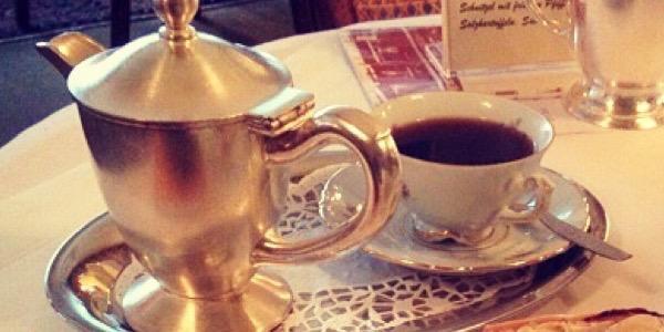 Kleines silberne Kaffeekännchen und kleine Tasse auf Tisch