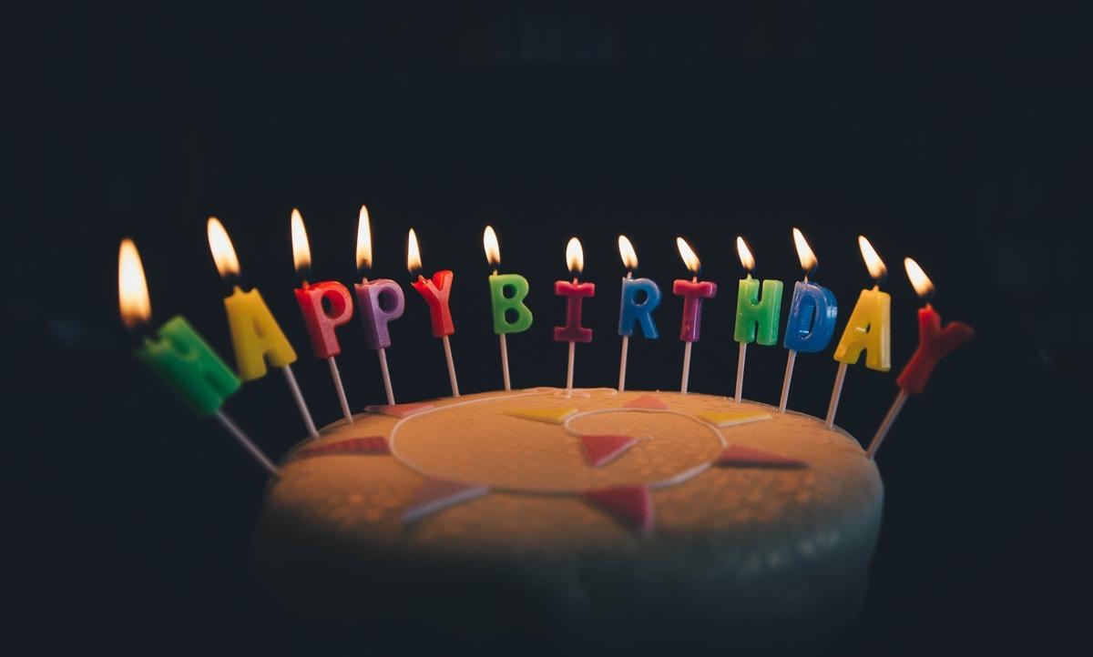 Eine Torte mit Kerzen aus Buchstaben, die Happy Birthday ergeben